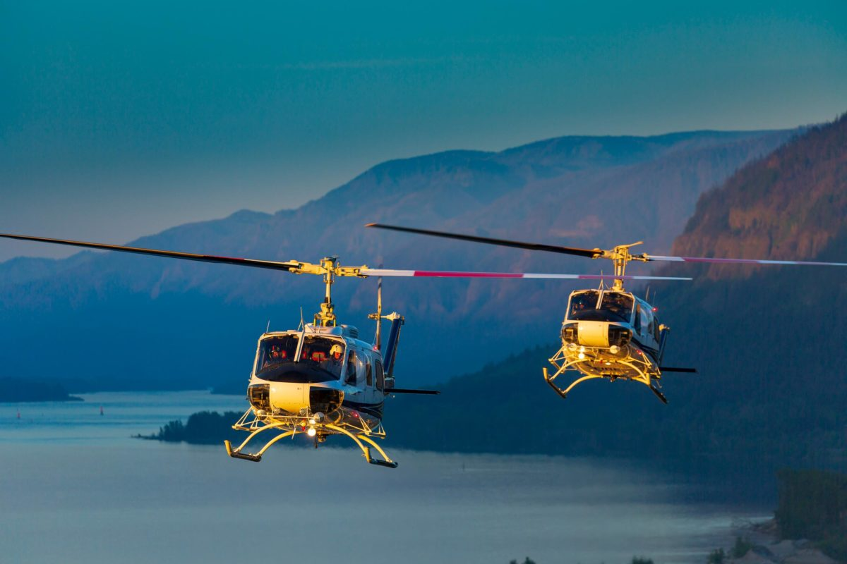 two helicopters flying over water and mountains