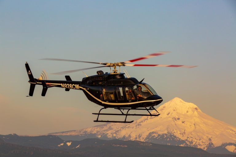 bell 407 helicopter flying past mountain