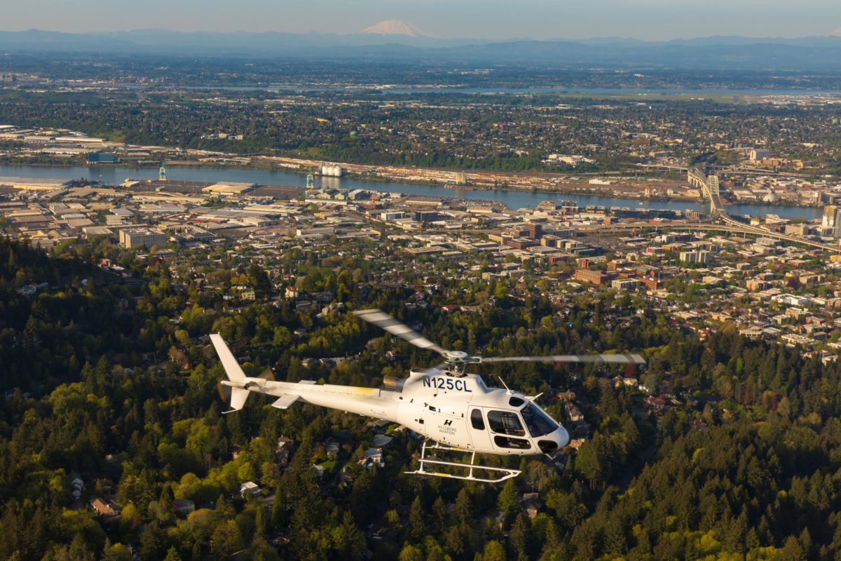 helicopter flying over city, river, trees
