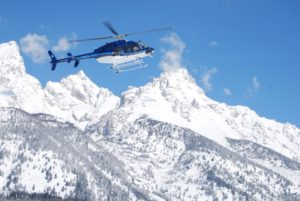 helicopter flying over snowy mountain