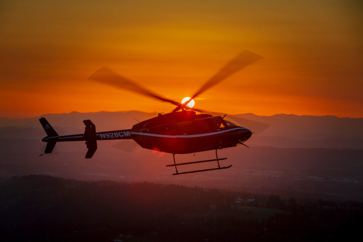 helicopter flying across sunset
