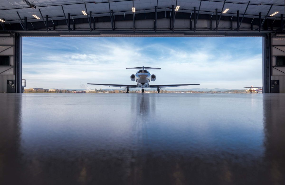 airplane coming into hanger with sky background