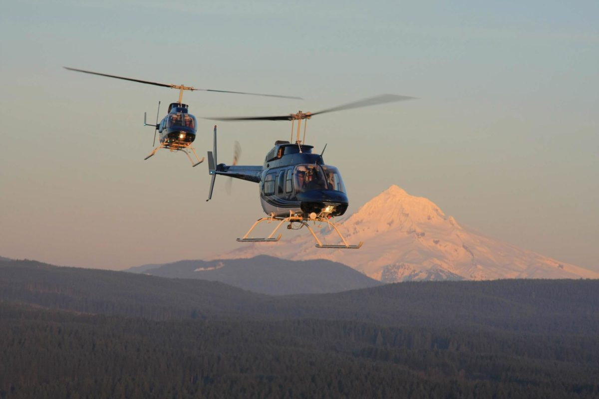 helicopters flying past mt. hood at sunset