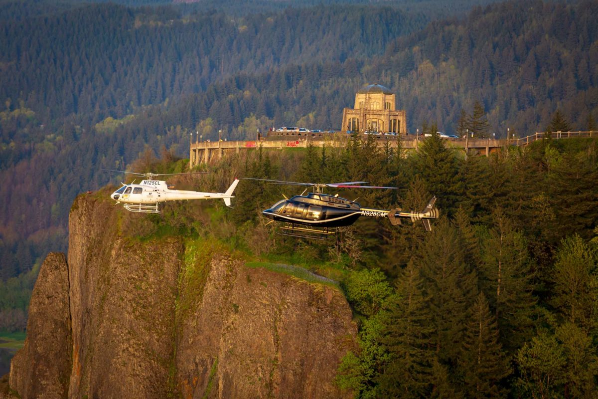 two helicopters flying across forested landscape and cliffside building