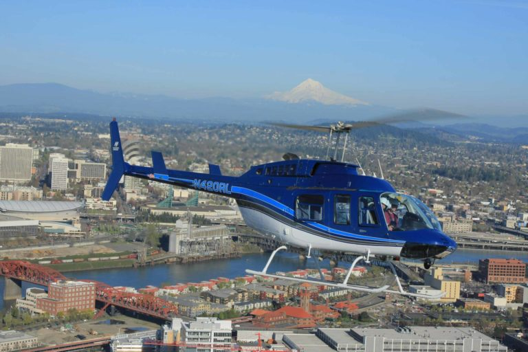 bell 206l3 flying over portland with mt. hood in bckground