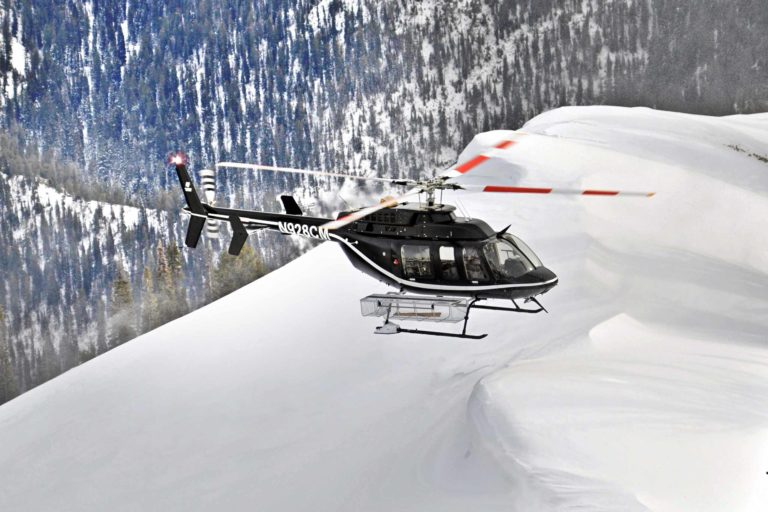 helicopter flying over snowy mountain terrain