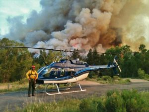 person standing with helicopter in front of billowing wildfire