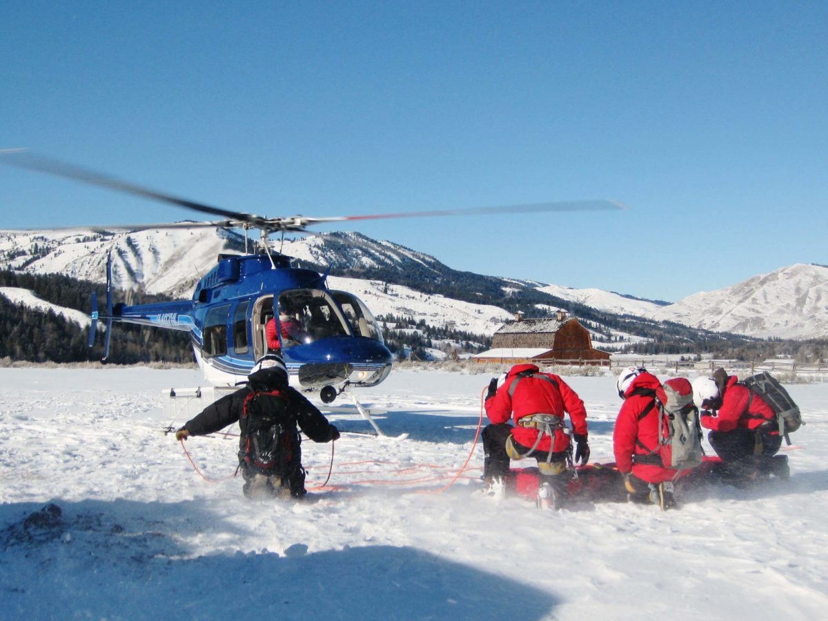 rescue crew and helicopter in snow