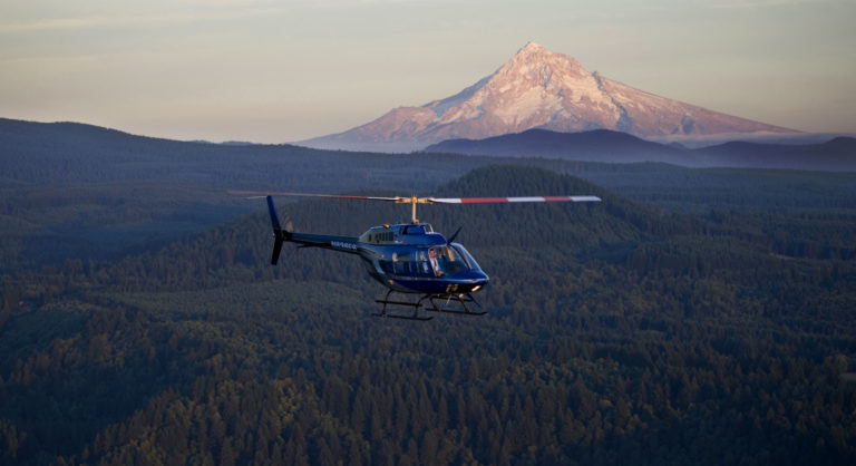 helicopter flying past mountain and forested landscape